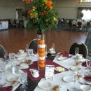 Tall centerpiece: cylendar filled with orange and white baby pumpkins. Flowers are orange lillies, yellow alstromeria, rust mums, burgundy hypericum berries, yellow solidago, grasses and branches