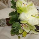 green cymbidium orchids with white roses, lime green button mums, brown monkey tail, scented geranium, brown satin ribbon with antique brooche.