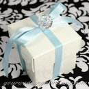 A glossy wedding favor box wrapped in blue satin ribbon and accented with an acrylic diamond charm.