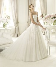 BARROCO Elegant brides will find the dress they have always dreamed of in Barroco by Pronovias 2012. The v-neck is created by spectacular embroidered bands in silver gemstones. Delicate embroidered flowers are applied over the soft chiffon draping that form the bodice of the dress, ending just above the waist. A large, modern skirt with asymmetric gathers makes the low waist even more dramatic. The dress is fastened at the back, corset style.