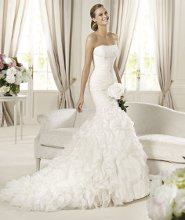 DAVINIA Davinia by Pronovias 2013 envelops and enhances the silhouette and is a sensual, romantic choice. The delicate strapless neckline and bodice are subtly embellished with embroidered tulle and gemstone appliqué. The bodice consists of lovely chiffon draping that trace the bride's curves and beautify the décolletage. The finishing touch to this flattering mermaid wedding dress is a spectacular skirt with degradé frills.