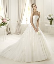 DONAIRE The Donaire wedding dress by Pronovias 2013 is ideal for a romantic day. The strapless neckline is edged with delicate tulle, a wonderful detail that accentuates the beautiful lace that decorates the bodice. This princess line wedding dress is flattering to the bride's shape, cinching the waist and smoothing the hips. The spectacular skirt has numerous layers of tulle that give it a light, flowing appearance.