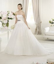 URIKA This princess wedding dress is made in tulle and delicate rebrodé lace. Urika, from the Glamour by Pronovias 2013 collection has a flattering off-the-shoulder neckline and original grosgrain belt decorated with silver beading. The dress has an exquisite lace-up back that emphasizes the fall of the tulle skirt. The romantic style of this dress comes from the delicate cascade of decorative details.