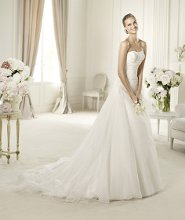 USIRIA The romantic style of this wedding dress comes from its original draped bodice. The Ursiria model from the Glamour by Pronovias 2013 collection has a wonderful sweetheart neckline in rebrodé lace, decorated with delicate beading. The flared skirt of this dress has a flattering lace-up back. The front of the skirt has side gathers and a wonderful half-train.