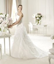 UTICA This flared wedding dress has a flattering off-the-shoulder neckline that enhances the wonderful shape of this gown. Utica, from the Glamour by Pronovias 2013 collection is a dream in delicate silk garza. The shoulders and hips are decorated with showers of original silver and white beading appliqués. The wonderful lace-up back gives it a modern look. Delicate embellishments at the hip mark the start of an elegant skirt with lovely, narrow frills.