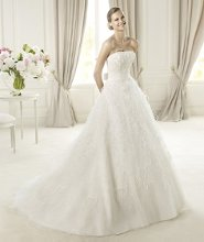 UCIFA Ucifa by Pronovias 2013 has a romantic off-the-shoulder neckline. The bodice is made of draped tulle with flower and feather appliqués. This A-line dress has a plain grosgrain belt with a bow at the back, that emphasizes the waist of the flared skirt with its cascading appliqués.