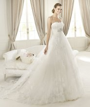 DECADA The Decada model from the Pronovias 2013 collection features spectacular embroidery that highlights the beauty of the strapless neckline and its frothy tulle skirt. The combination of these two garments gives the ensemble an exquisite, romantic tone, accentuated by stunning lace and embroidery. The skirt of this empire waist wedding dress features a layer of semi-transparent tulle that reveals the inner skirt below the draping around the bride's waist.