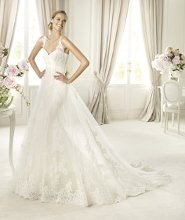 PETUNIA Petunia from the Costura by Pronovias 2013 collection has a sweetheart neckline with rebrodé lace straps and an original two-part skirt. Both the inner and outer skirts are decorated with beautiful lace appliqués and a scalloped hem. This wedding dress, created in tulle and lace, has a bodice with soft draping that accentuates the empire line of the design.