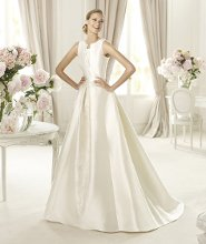 UBAGO This wedding dress features delicate folds that give shape to the hem and the wonderful bateau neckline. Ubago from the Costura by Pronovias 2013 collection is a beautiful A-line wedding dress with delicate soutage embroidery. It is beaded and covered in delicate pleats and has square armholes that accentuate its exquisite elegance.