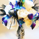 Blue orchids, white roses, black feathers and damask wrap.