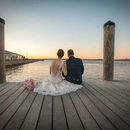 130x130 sq 1519847187 175c4702ae8c5526 1514488025475 bride and groom sitting on docks at sunset farth