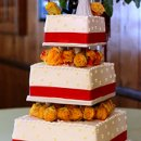 130x130_sq_1326143859838-weddingcakeredribbonorangeflowerswhitecake