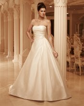 Style: 2101 Textured Satin, strapless A-line gown with a sweetheart neckline. The bodice is pleated with an asymmetrical waist seam. Matching fabric buttons line the back of the gown.