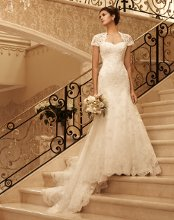 Style: 2102 This gown has an attached short sleeve Queen Anne neckline with keyhole back. Sweetheart neckline is trimmed with pleated organza. Beaded lace fit and flare gown is finished with an eyelash fringe scalloped hemline.