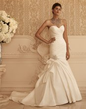 Style: 2106 Trumpet silhouette with an asymmetrical, ruched, Textured Satin bodice. An alternating pattern of crystal and faux beaded buttons trail along the zipper. The front and back skirt features a crystal, rhinestone, and pearl appliqué.