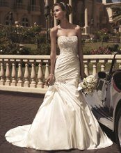"Style: 2104 This gown has a heavily beaded bodice full of Swarovski Crystals, rhinestones, and pearls. Soft sweetheart front neckline with a ""V"" back neckline shape. A draped Perfecting Satin skirt is accented by pick-ups and beaded appliqué. The zipper is lined with faux beaded buttons."