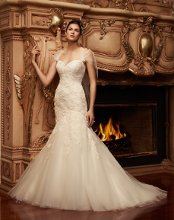 Style: 2113 Strapless sweetheart neckline gown with an asymmetrical mermaid silhouette and a beaded Shimmery Lace overlay. The bodice is lined with criss cross pleating under the lace and the skirt is layered with tulle. This gown comes with a detachable sheer tulle shawl with lace detail.