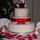 Christmas Eve Wedding at Castleton, top and bottom layer covered in coconut. Ribbon is Red Satin and flowers arranged by KC Confection.