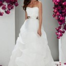 1758  <br /> Mikaella Satin and Organza bridal gown. Strapless asymmetrical pleated bodice with beaded Guipure appliqué, ribbon and flower embellishment at natural waist. Organza cascade full skirt. Sweep Train.