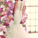 Style 1904  Mikaella Re-embroidered Lace and Organdy Wedding Dress. Lace tunic bodice. Lace illusion halter neckline with back keyhole opening. Organza ruffled skirt with mohair detailed edging. Covered button and loops over zipper. Chapel Train. Available colours: Pearl.