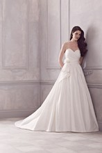 4415  Silk Dupioni Strapless cross-over Bridal Gown. Ruched bodice with Removable side drape with flower embellishment. Gathered skirt with side pockets. Covered buttons over zipper. Cathedral Train.