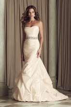 4453  Silk Dupioni bridal gown. Strapless tunic bodice with removable beaded sash at natural waist. Cascade skirt with bubble hem. Covered buttons and loops over zipper. Chapel train.