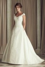 4454  French Alençcon Lace and Silk Dupioni bridal gown.Beaded v-neck dropped waist lace bodice with cap sleeves and low back. Flat front and pleated back Dupioni skirt. Side pockets. Cathedral Train.