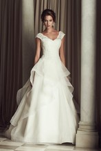4458  French Alençon Lace and Organza bridal gown. Beaded v-neck drop waist lace bodice with cap sleeves. Full organza skirt with cascading mohair detailed edging. Chapel Train.