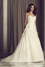 4461  Silk Dupioni bridal gown. Crossover ruched bodice with full side pleated draped skirt. Side beaded flower embellishment. Covered buttons and loops over zipper. Cathedral Train.