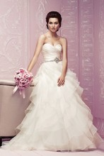 Style 4256   Silk Duchesse and Organza bridal gown. Strapless cross over pleated bodice with beaded appliqué at waist. Full Organza ruffled skirt with covered buttons over zipper. Sweep Train.