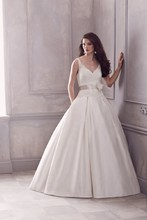 Style 4400   Re-embroidered Lace and Silk Dupioni Gown. Sleeveless V-neck dropped waist bodice. Double box pleated full skirt. Removable ribbon and flower embellishment at natural waist. Side pockets. Chapel Train.