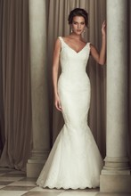 4451 Paloma Re-embroidered Lace and Tulle bridal gown.Sleeveless V-neck tunic lace bodice. Flare skirt with cascading lace appliqués and hemlace. Covered buttons and loops over zipper. Sweep Train.
