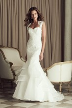 4455 French Alençon Lace and Organza bridal gown.Strapless sweetheart lace tunic bodice. Side tiered ruffle organza skirt with mohair detailed edging.Covered buttons and loops over zipper. Lace bolero included. Chapel Train.