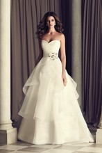 4465 Italian Taffeta and Organza bridal gown. Strapless cross-over pleated Taffeta bodice. Removable Italian Taffeta belt with side beaded flowerembellishment at natural waist. Full tiered organza skirt with mohair detailed edging. Chapel Train.