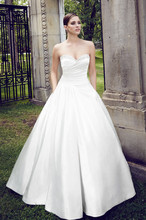 Style: 4556 Paloma Peau de Soie Wedding Dress. Strapless cross-over pleated bodice with beading across sweetheart neckline. Full side pleated skirt, pleated back, and side pockets. Covered buttons and loops over zipper. Cathedral Train.