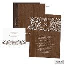 Tiny white flowers bloom on a brown wood grain background on this Jean M wedding invitation for a sweet and natural look.