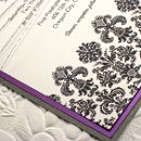This distinctive wedding invitation is adorned along the bottom with a wide damask band with a velvet appearance. Invitation is printed on 130lb cardstock, adorned by a silk metallic purple layer, and a final silver backing layered. Final product was wrapped in a silver hemp.