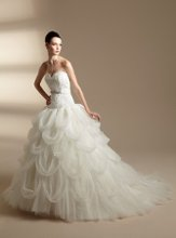 T142007 Strapless sweetheart neckline with lace appliques on bodice, detachable beaded waistband, and gathered layers on skirt.