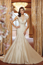 Style #y11413 Dream taffeta and richly embellished lace marry seamlessly in mermaid gown Selyse with dropped waist. Sheer tulle and scalloped lace cap sleeves spill into a plunging V-neckline, subtly softening the sweetheart bodice with hand-beaded accent under the bust. For the bride who wishes to make her groom swoon with desire, Selyse also features a dramatic keyhole back finished with a zipper trimmed with diamante buttons.