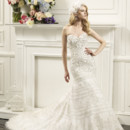 D8058 This fit and flare features a defined sweetheart neckline and curve enhancing accents. Lavish lace appliques and rich embroidery are encrusted with Swarovski crystals that embellish throughout the entire gown.