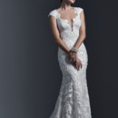 Vidonia  Dramatic laser cut lace appliqués lay atop tulle in this form-fitting sheath wedding dress, with demure illusion back. Finished with plunging neckline and covered buttons over zipper closure.