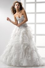Topaz - JSM1481 This fashion-forward, peek-a-boo bodice adorned with bead-encrusted lace appliqués speaks to your inner diva. Layers of Tuscan Organza with finished edging flutters throughout the full A-line skirt. Sweetheart neckline with corset closure featuring Swarovski crystals.