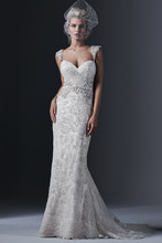 Demetria Elegant tulle and lace combine to create this stunning sheath wedding dress, accented with a Swarovksi crystal motif at the waist. Finished with dramatic sweetheart neckline and covered buttons over zipper and inner elastic closure. Beaded embroidered, cap-sleeve shoulder straps offered separately.