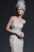 Zinnia  Dramatic lace appliqués on tulle, embellished with dazzling Swarovski crystals and pearls, drift down the length of this fit and flare wedding dress. Finished with scoop neckline and crystal buttons over zipper and inner corset closure.