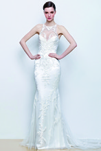 ISLA This form-fitting gown has a high illusion neckline covered in white floral appliqués, and adorned illusion back .
