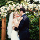130x130 sq 1528128102 10239c860d236671 1444674084155 bride and groom kiss beneath rose adorned arbor.