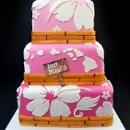 Just Maui'd - Featuring white hibiscus flowers and bamboo trim, this wedding cake's tier graduate from darker to lighter as they go up, and the hawaiian islands are placed on the middle tier with a little beach sign that announces the couple's marriage.
