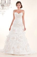 3148 Gwendolyn This exquisite gown has a beautifully ruched bodice and strapless sweetheart neckline. The silk bodice is complimented by a low back and dramatic organza flowers on the skirt. Shown in Diamond White.