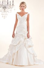 3159 Sarita This ravishing pleated silk gown features a deep V and wide off-the-shoulder straps. The dropped waist is highlighted with a lace and organza flower and flows into a full bustled skirt. Shown in Diamond White.