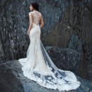 Spring 2014 Aurora - Back Mermaid gown of buttercup silk shantung and a re-embroidered French Alençon lace. Sheer mermaid overlay with a re-embroidered French Alençon lace asymmetric applique over an exposed back and climbing up the train.